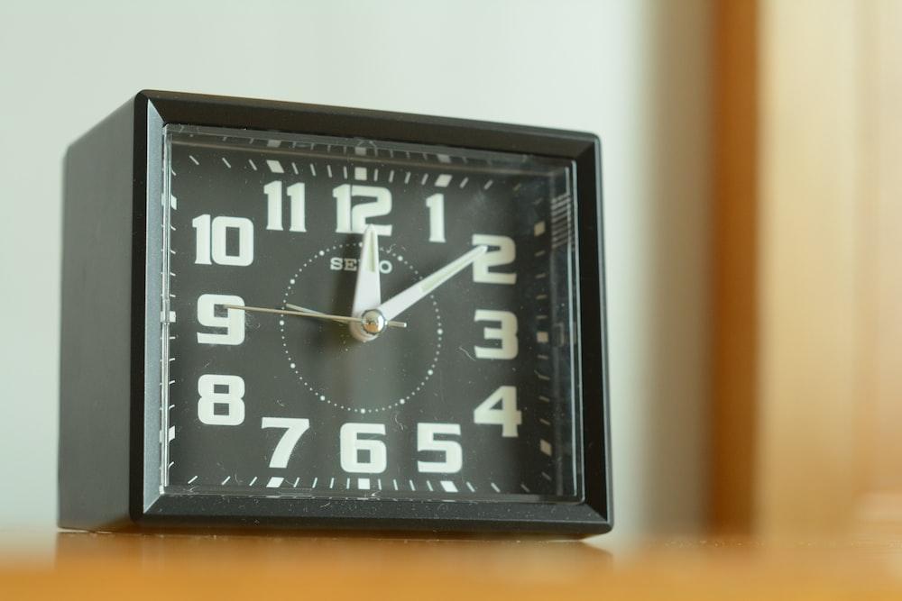 square black analog desk clock 12:05 o'clock