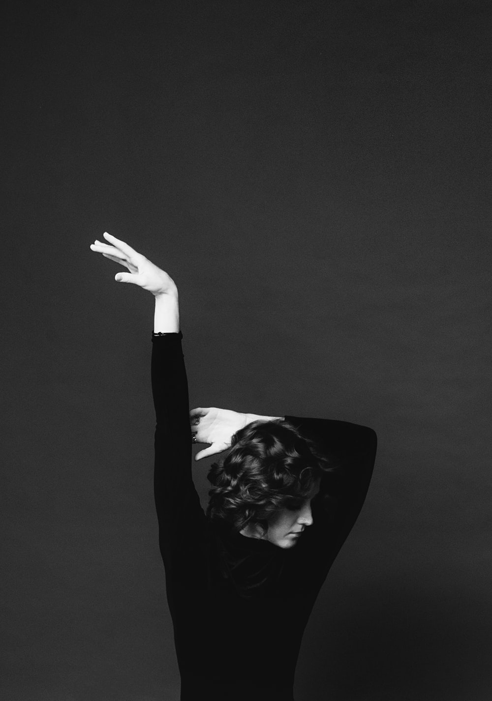 grayscale photo of woman in long-sleeved shirt posing