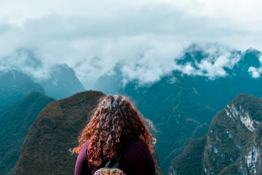 woman facing the mountains during day