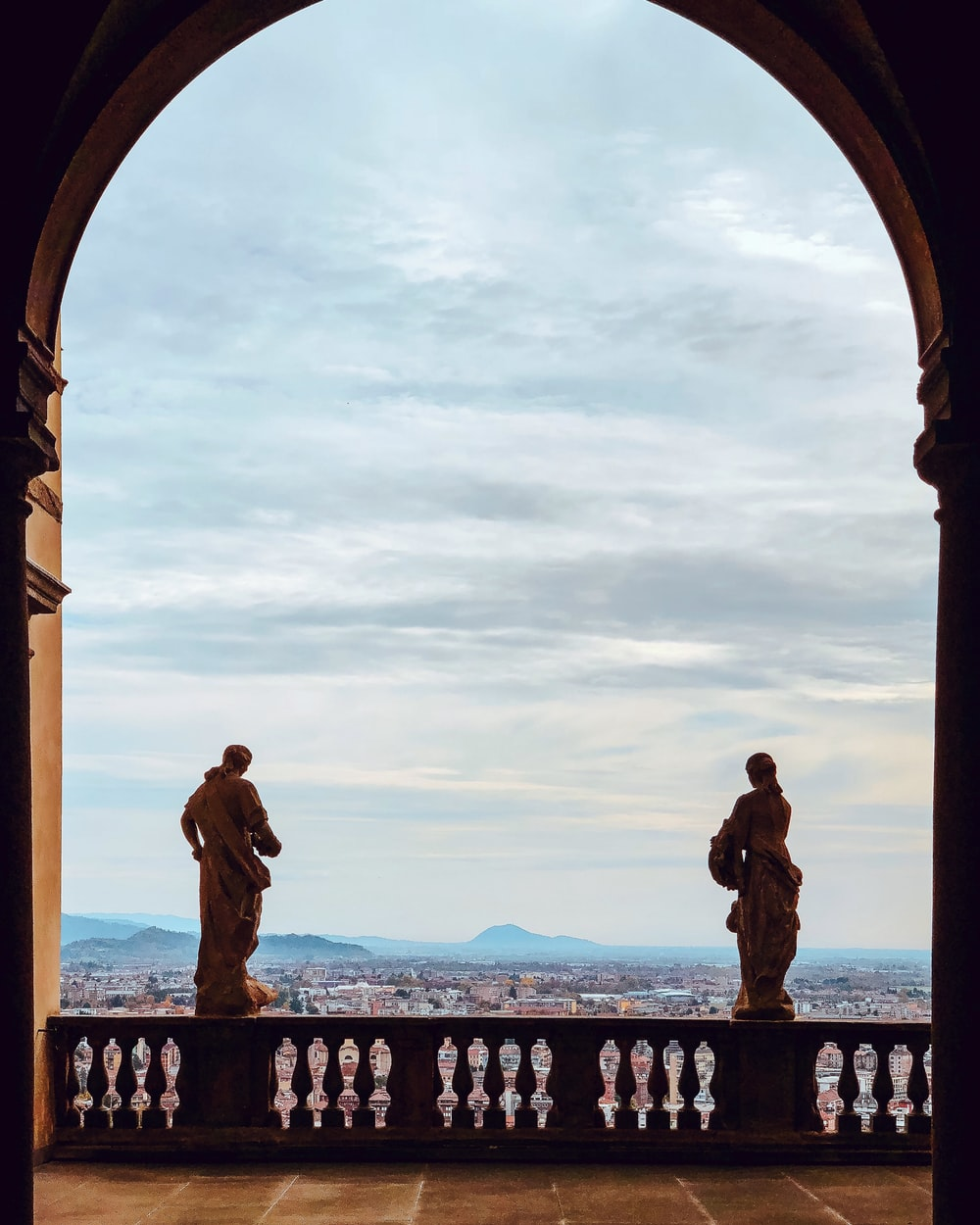 two statues on balcony railing during day