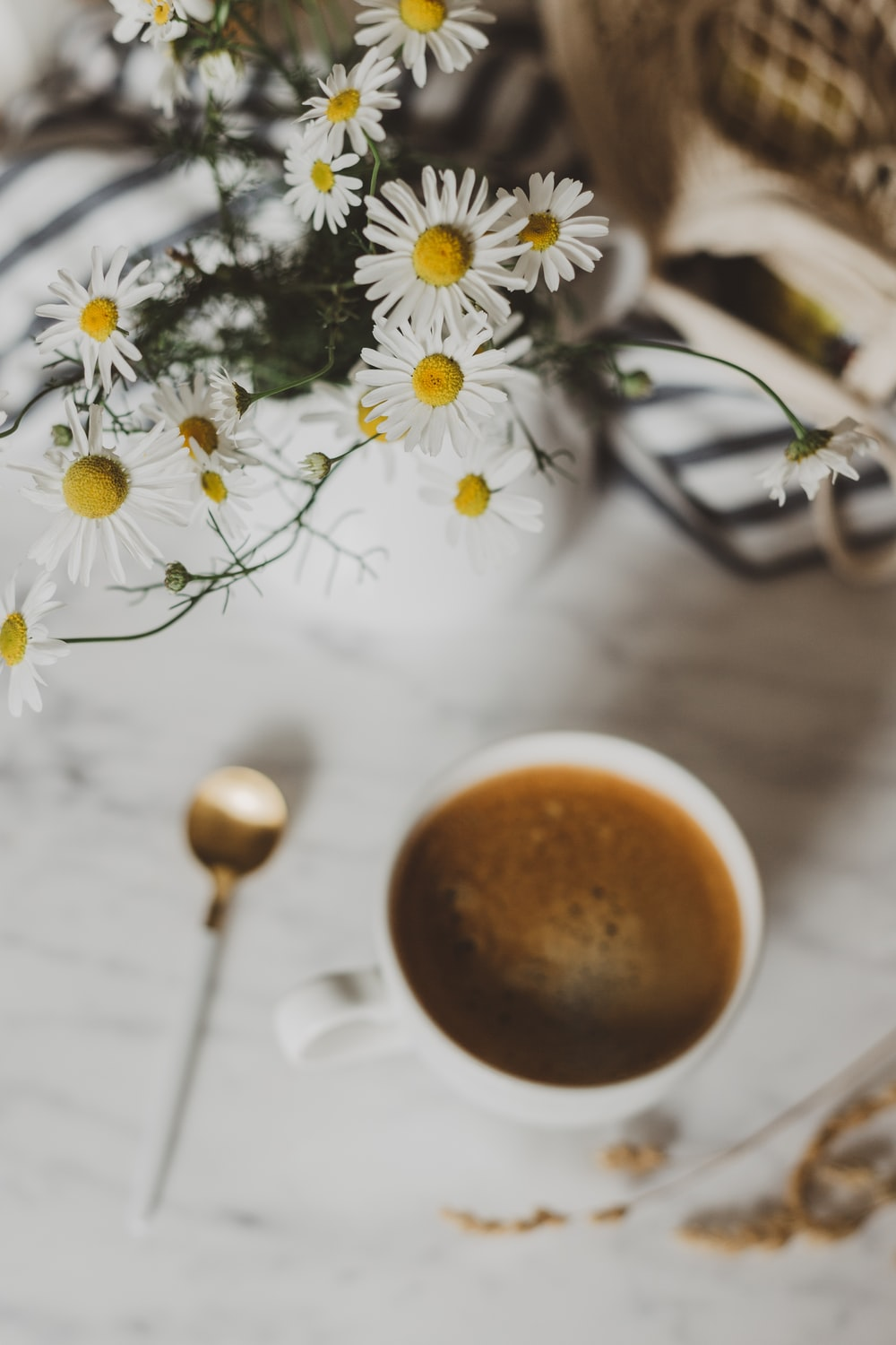 selective focus photography of white flower arrangement beside mug of coffee