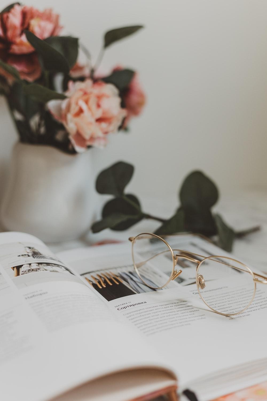 gold-colored framed eyeglasses on book