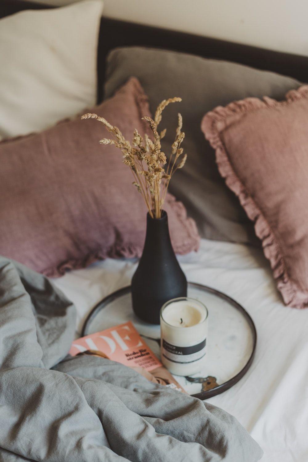 white candle beside brown vase on tray