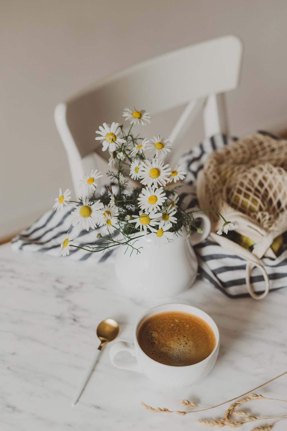 cappuccino near white and yellow flowers in vase on white table