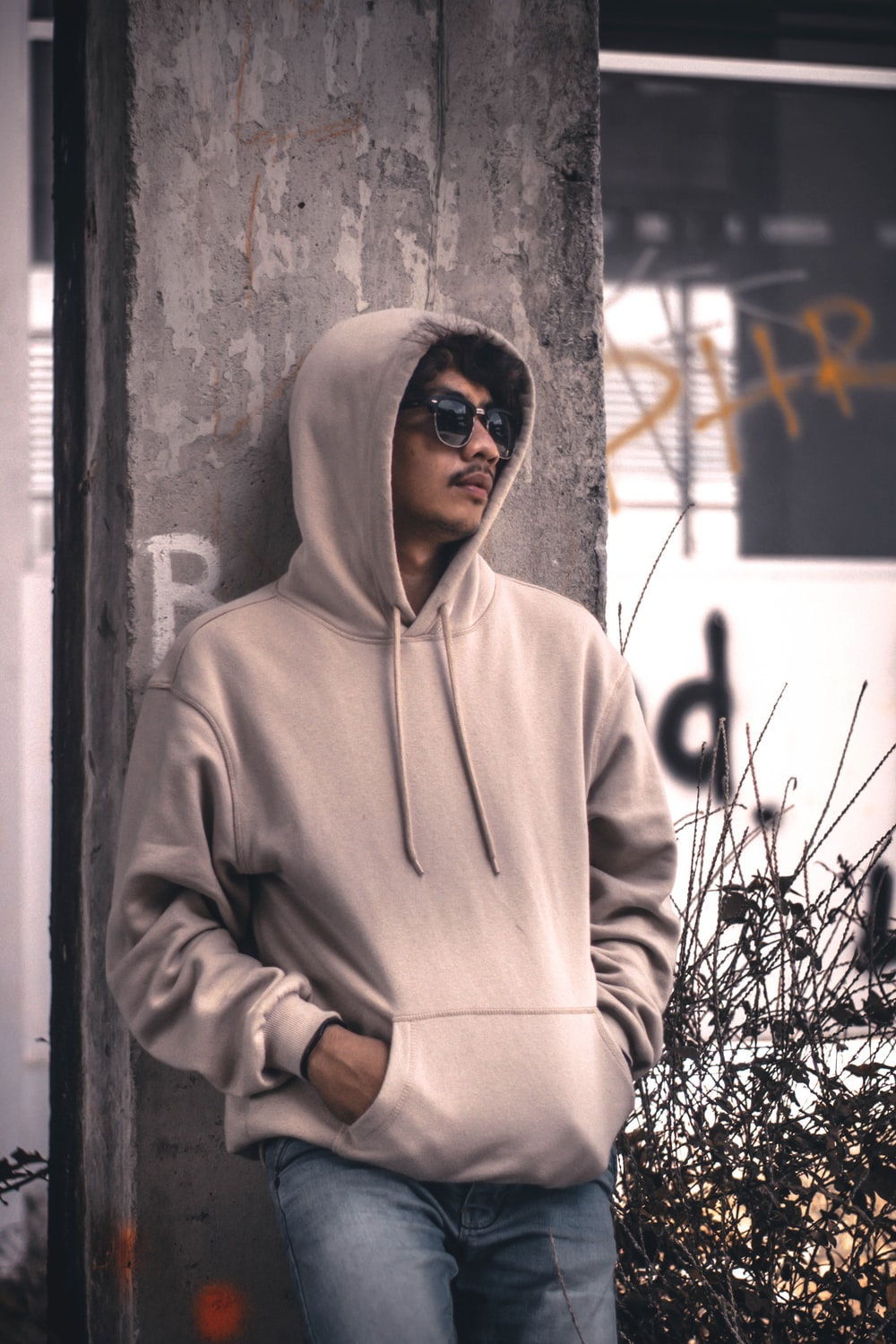 men wearing a grey hoodie jacket leaning in a wall during daytime