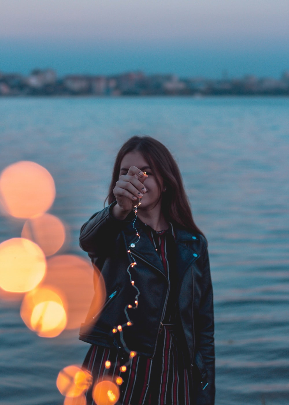 woman holding LED string lights near body of water