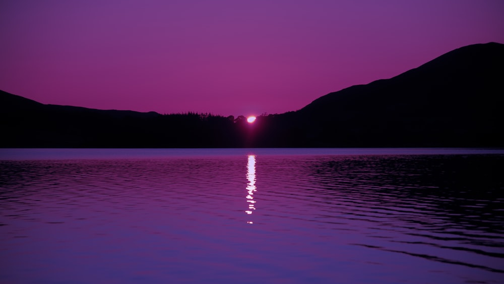 violet and black landscape photo of a sunset at a lake