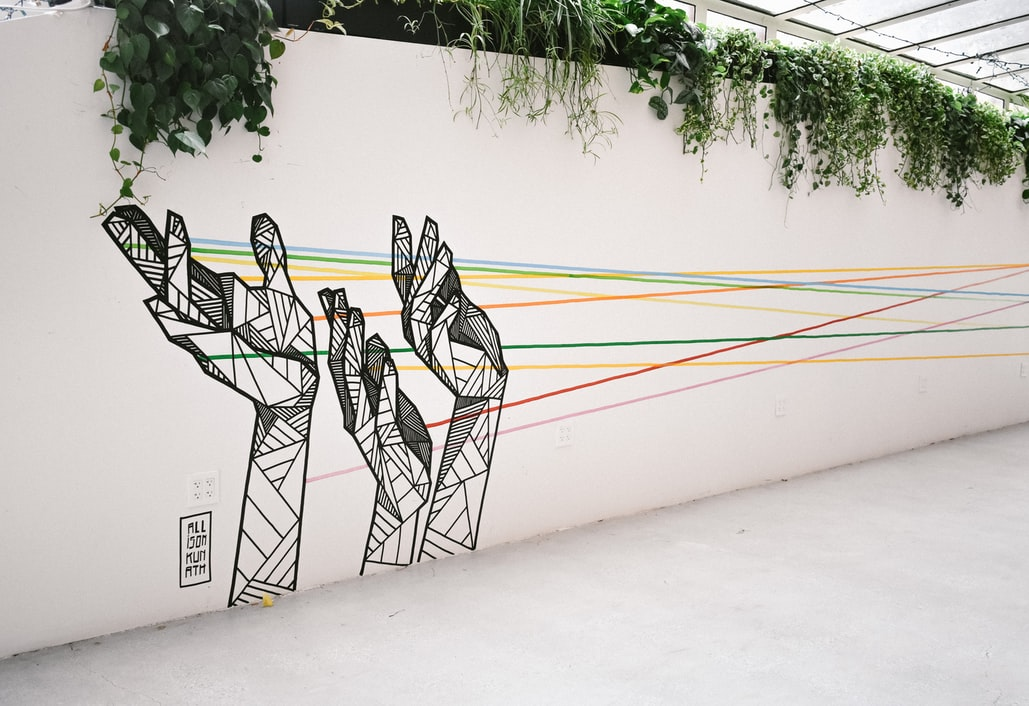 Mural of three geometric hands with rainbow strings coming from them, across a wall topped with ivy