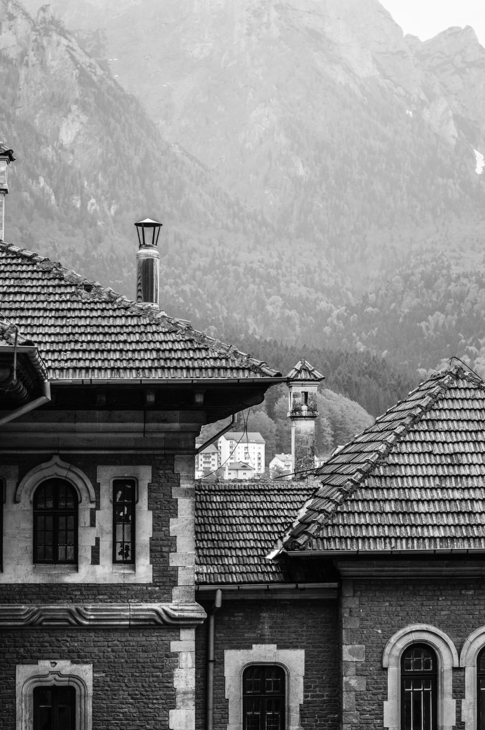 grayscale photography of house near mountain