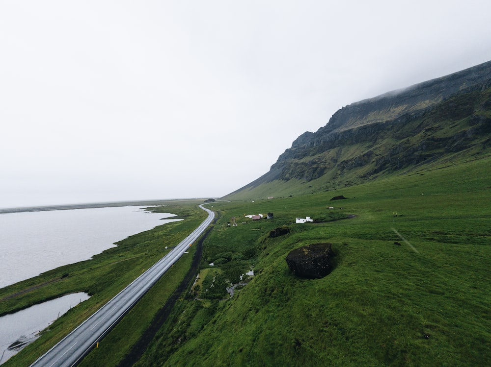 gray concrete road near green field viewing mountain and sea
