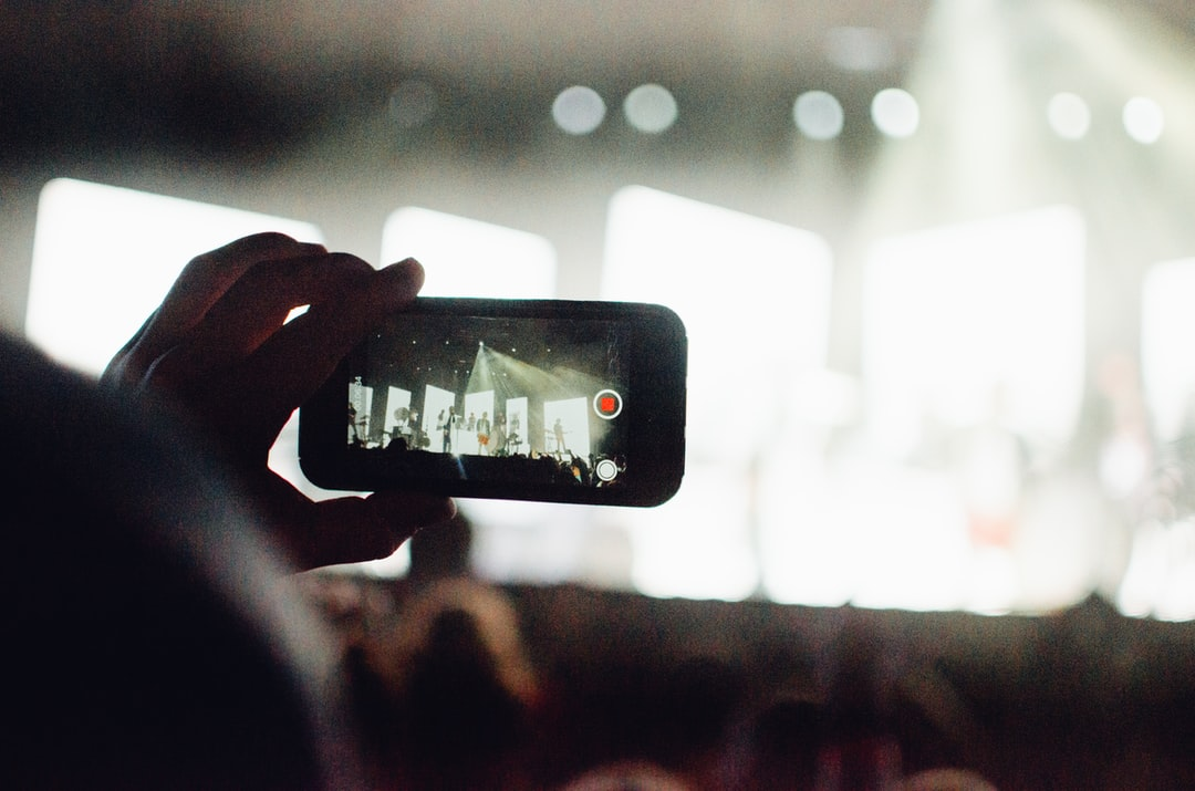This photo was taken at the ALIVE Christian Musical Festival in 2019. There were so many great concerts and so many good photos to be taken, but the real treat was seeing what the crowd took notice of and wanted to remember. This is a photo of a man taking a video of one of the concerts using his Apple iPhone, so that he could remember this moment for the rest of his life.