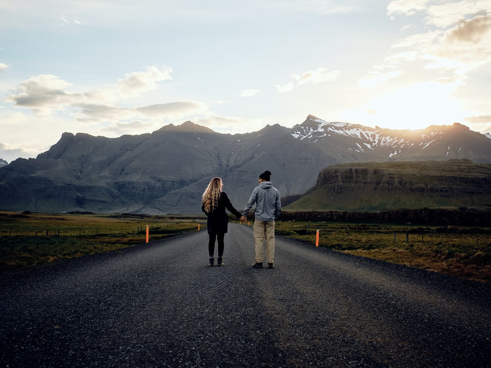 couple holding hands on road during daytime
