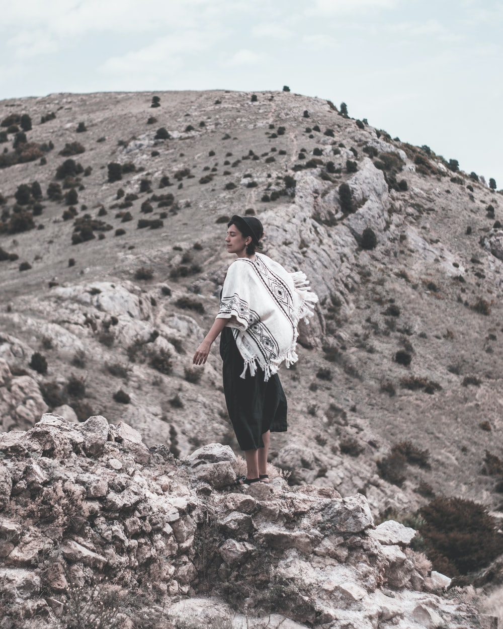 person in white top standing on mountain during daytime