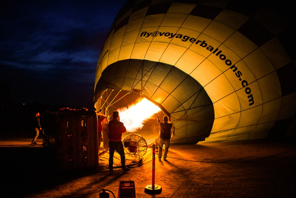 unknown persons standing near beside hot air balloon