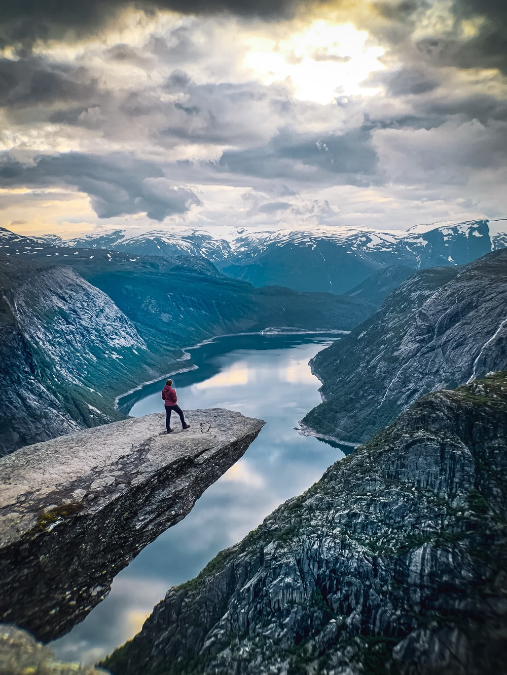 person standing on Trolltunga during daytime