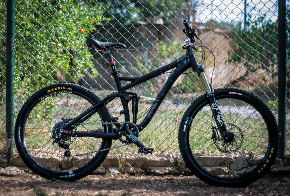 shallow focus photo of black full-suspension mountain bike parked beside fence