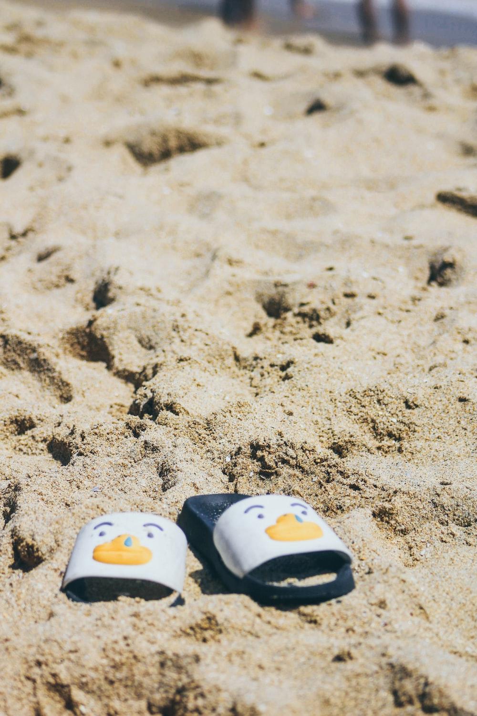 pair of white-and-black slide sandals on white sand