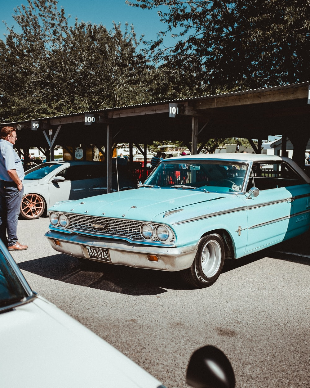 teal coupe parked on street