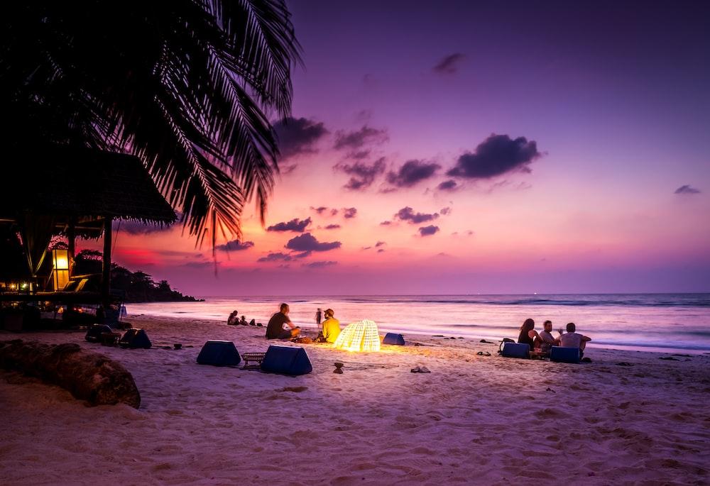 people sitting near seashore viewing sea under orange and blue skies