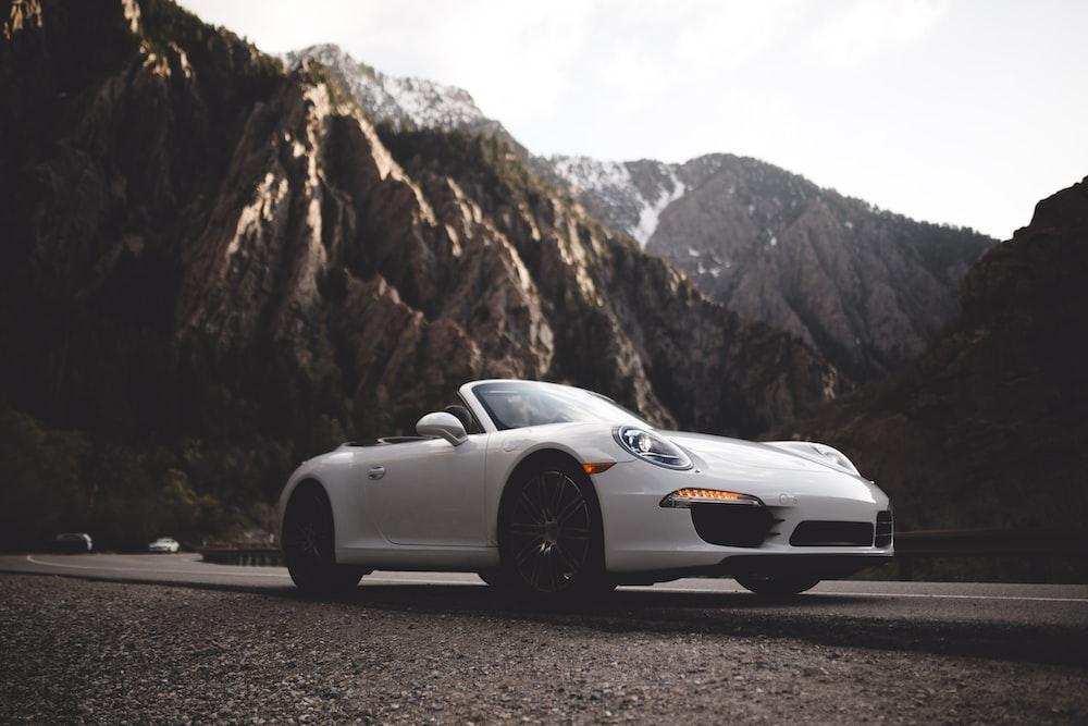 white Porsche convertible coupe on road