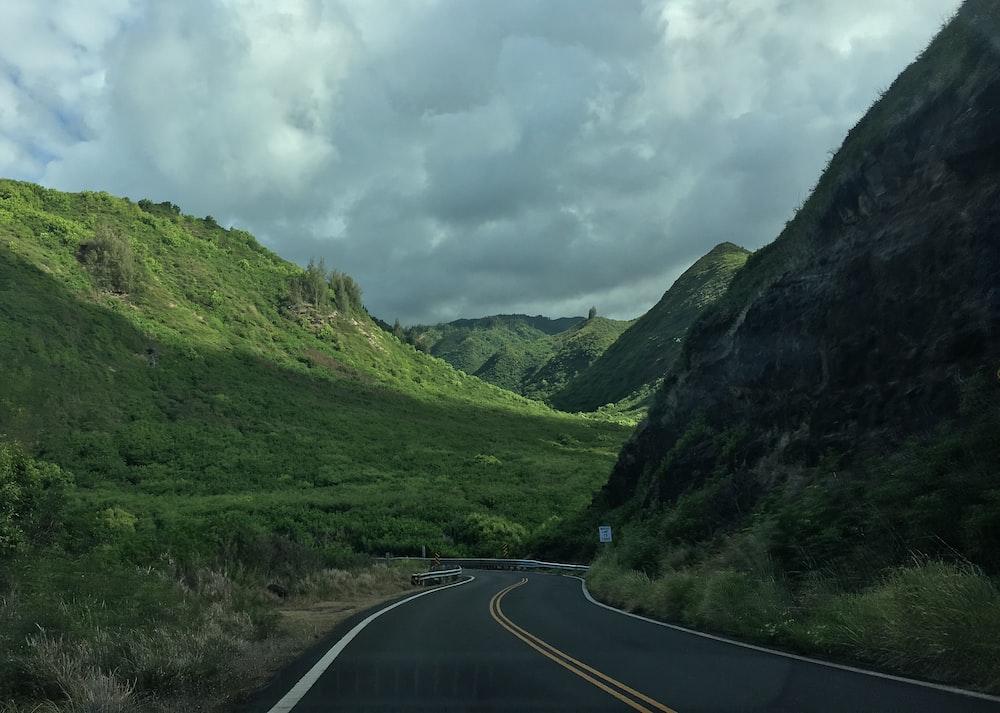 landscape photo of gray asphalt road towards mountains