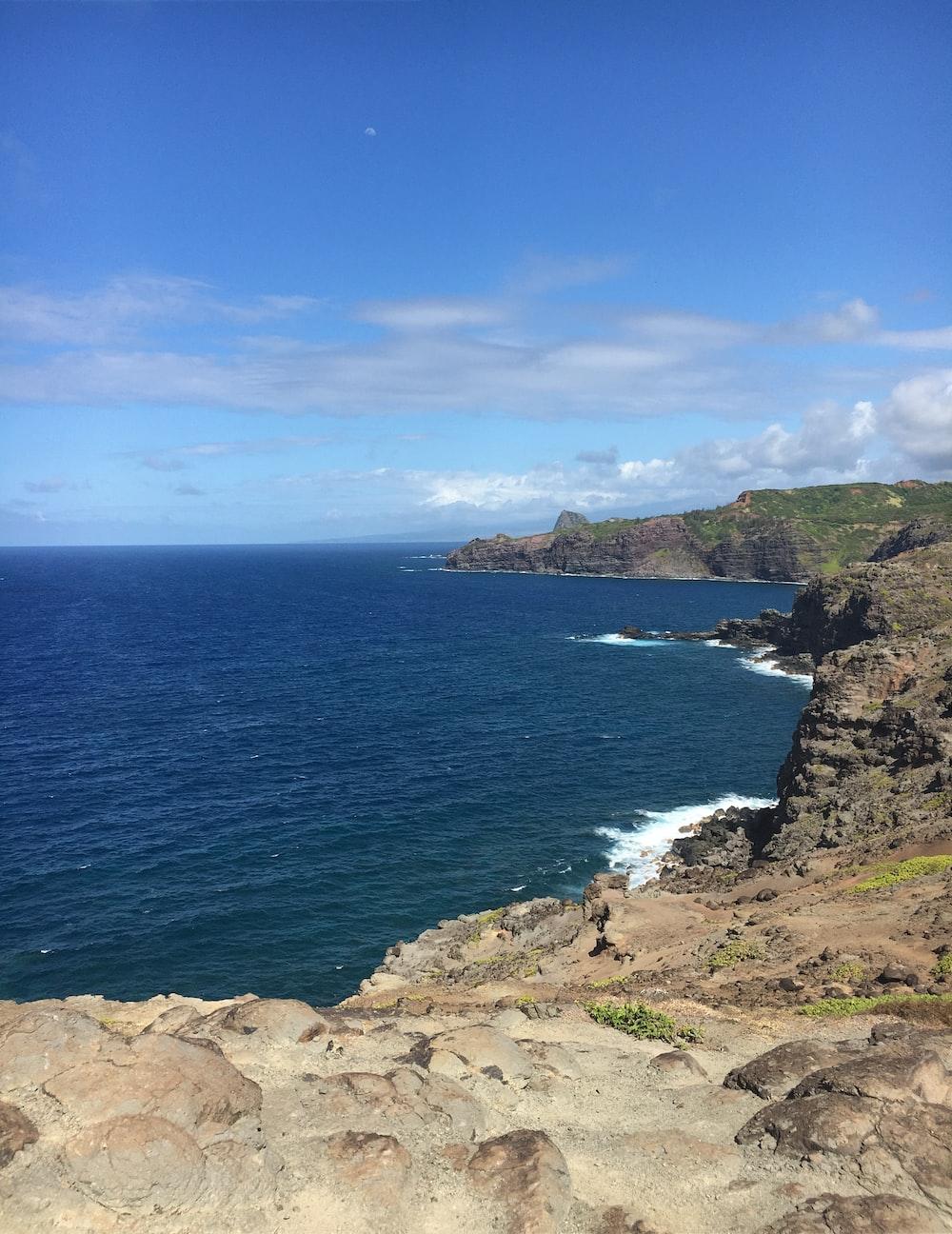 brown rock cliff beside ocean