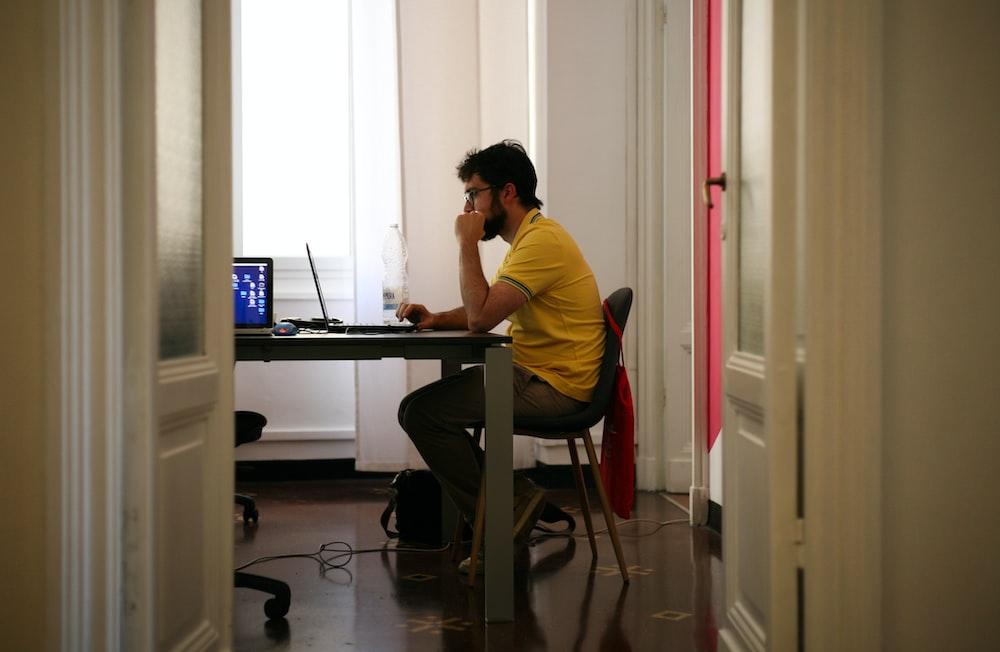 man siting facing laptop computer