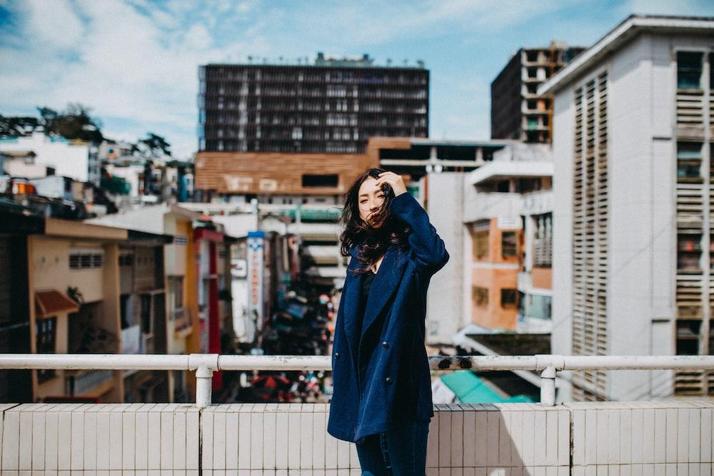 woman standing beside fence near building