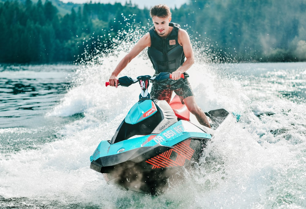 photography of man riding personal watercraft during daytime