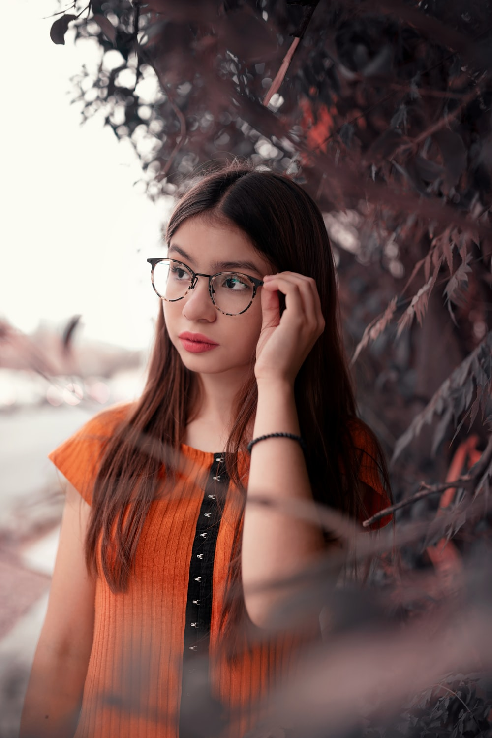 woman in orange and black top and eyeglasses