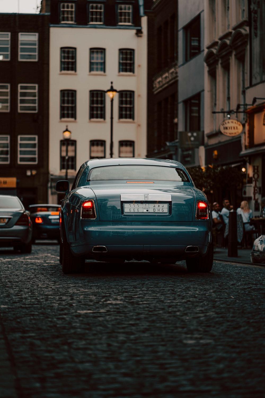gray car on road between buildings