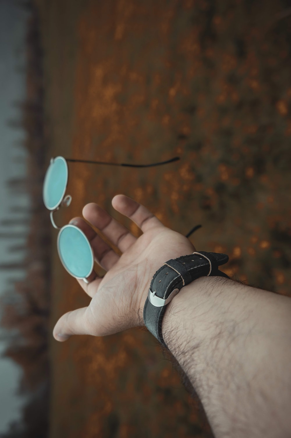 man holding hippie sunglasses