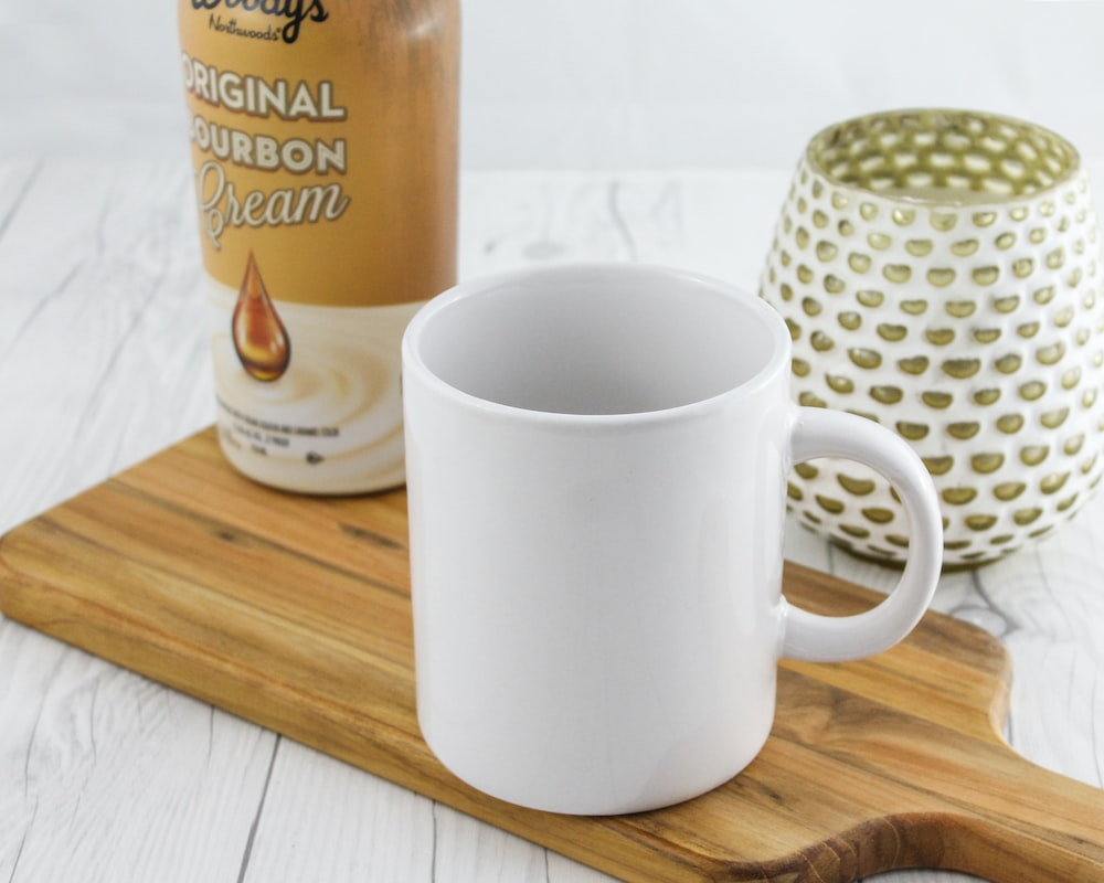 white mug near brown labeled can and vase close-up photography