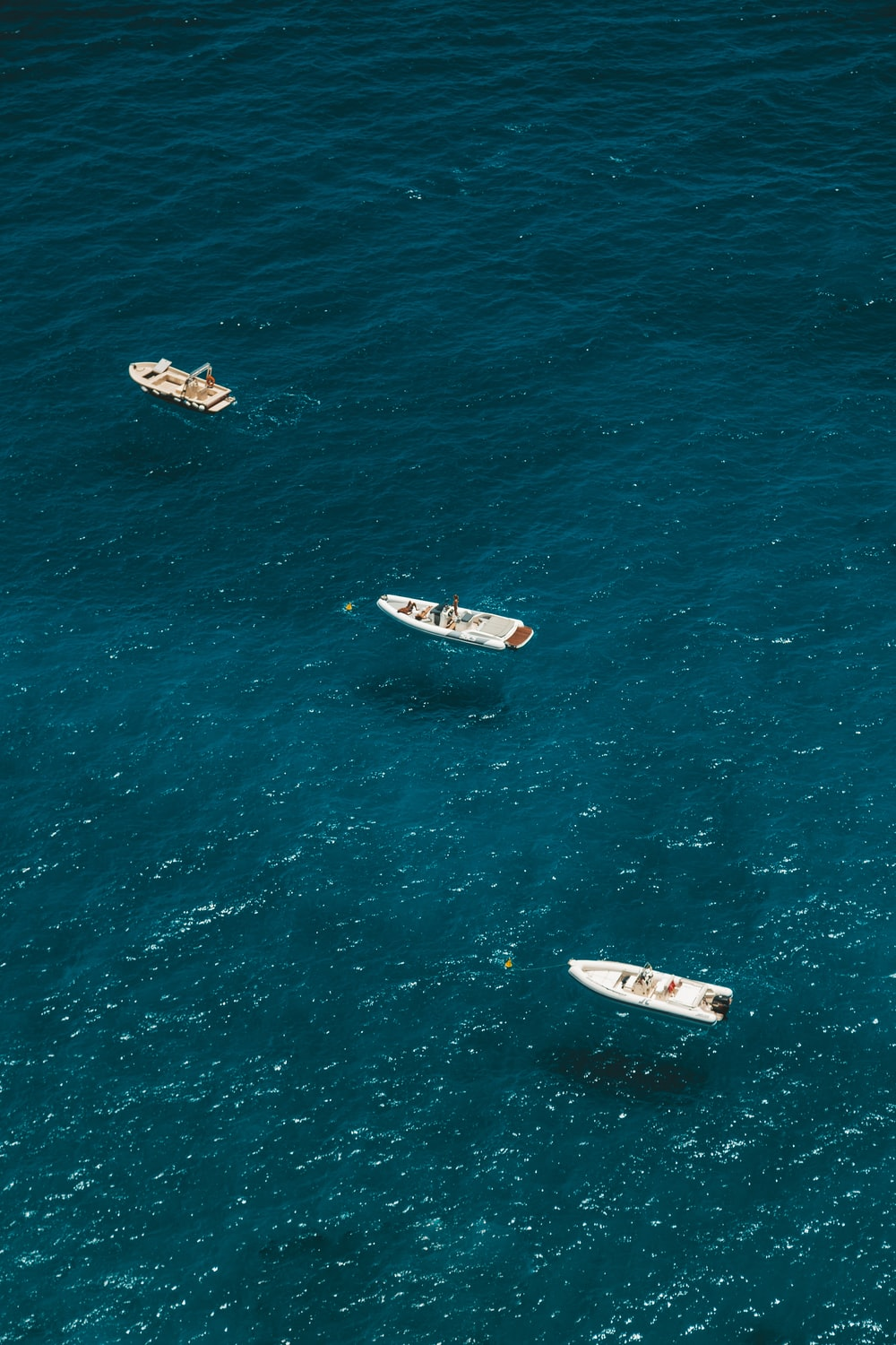 three white boats on body of water at daytime