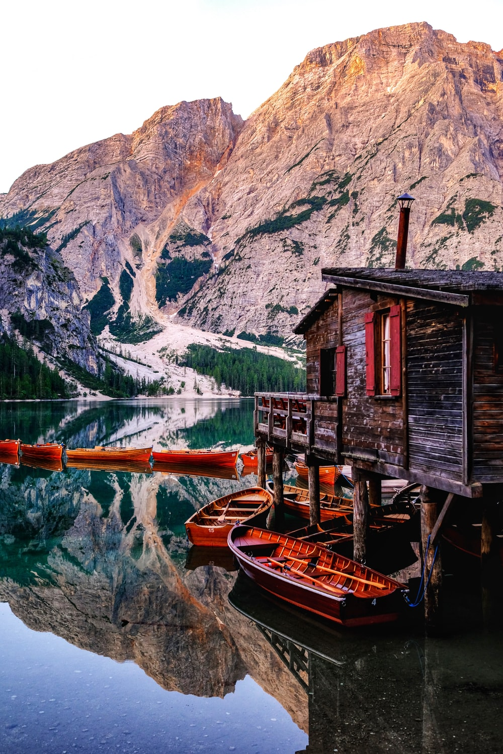 red wooden house beside body of water
