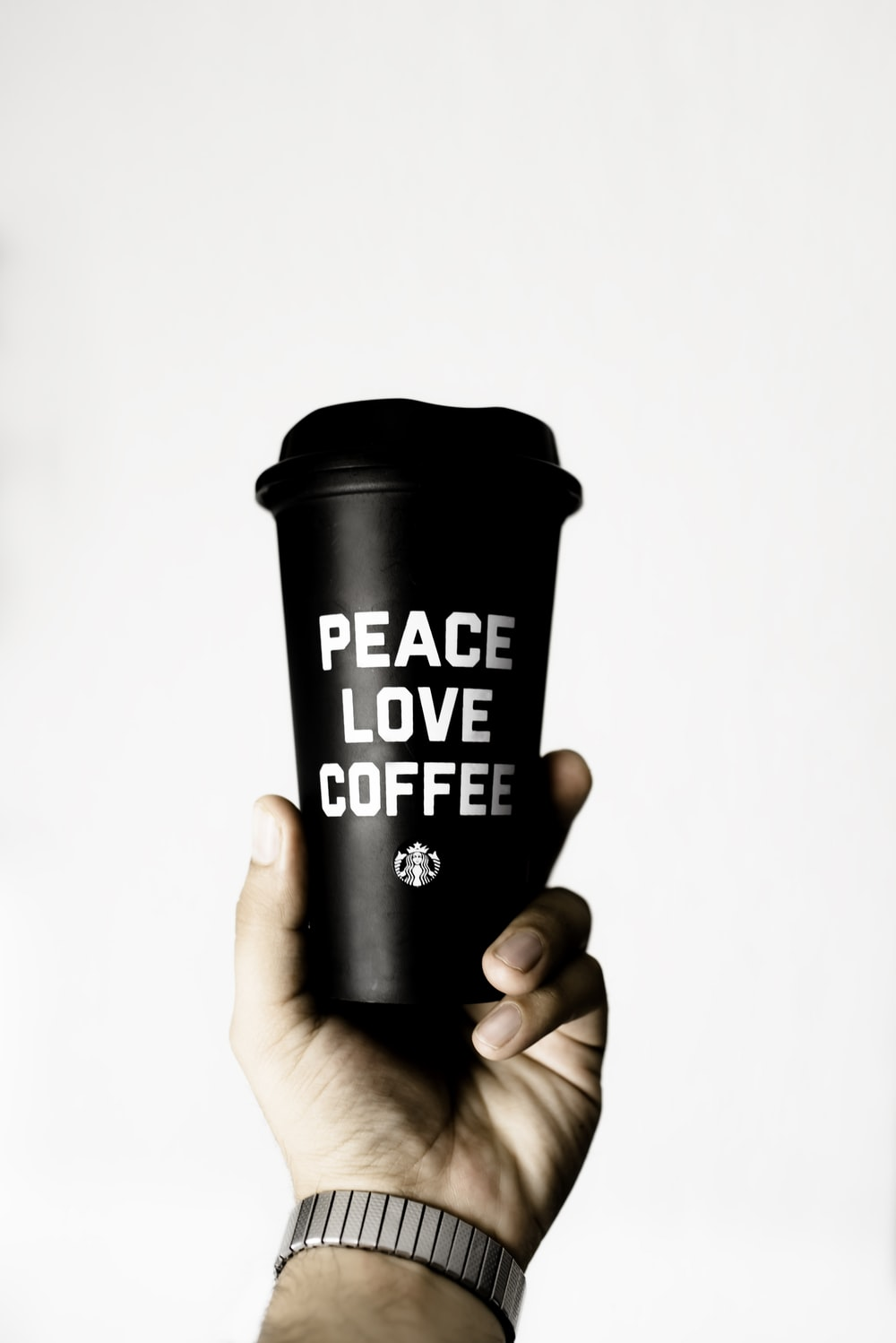 person holding peace love coffee-printed tumbler