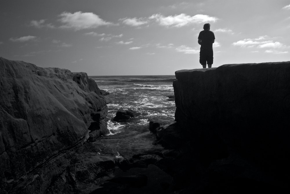 silhouette of man standing on rock