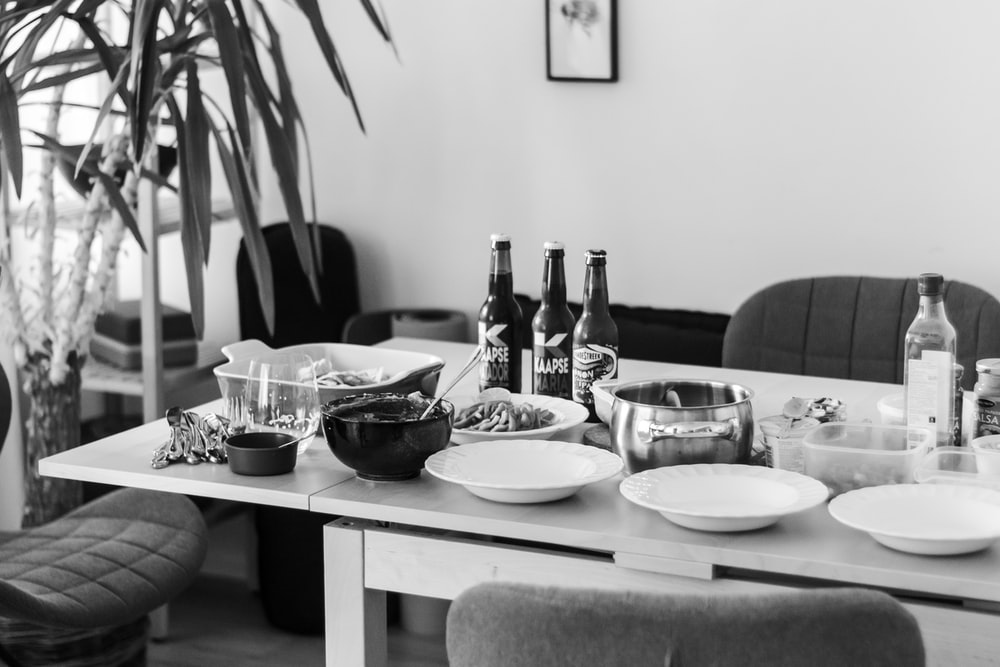 grayscale photo of dining table with plates and bowls