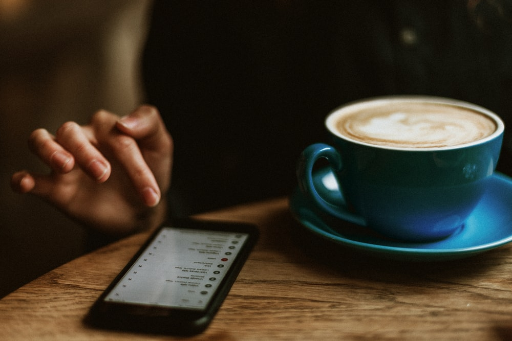 black iPhone 7 beside blue teacup with saucer and latte