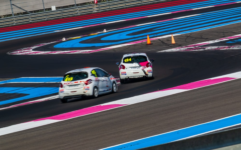 two white vehicles on race track during daytime