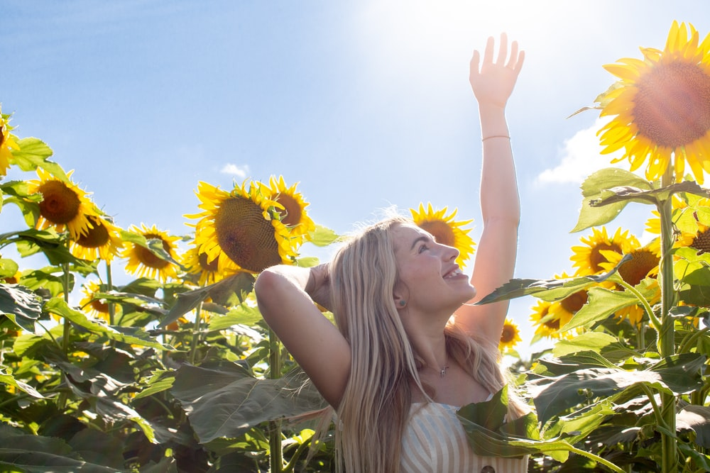 woman standing and raising her hand while smiling on sunflower field during daytime