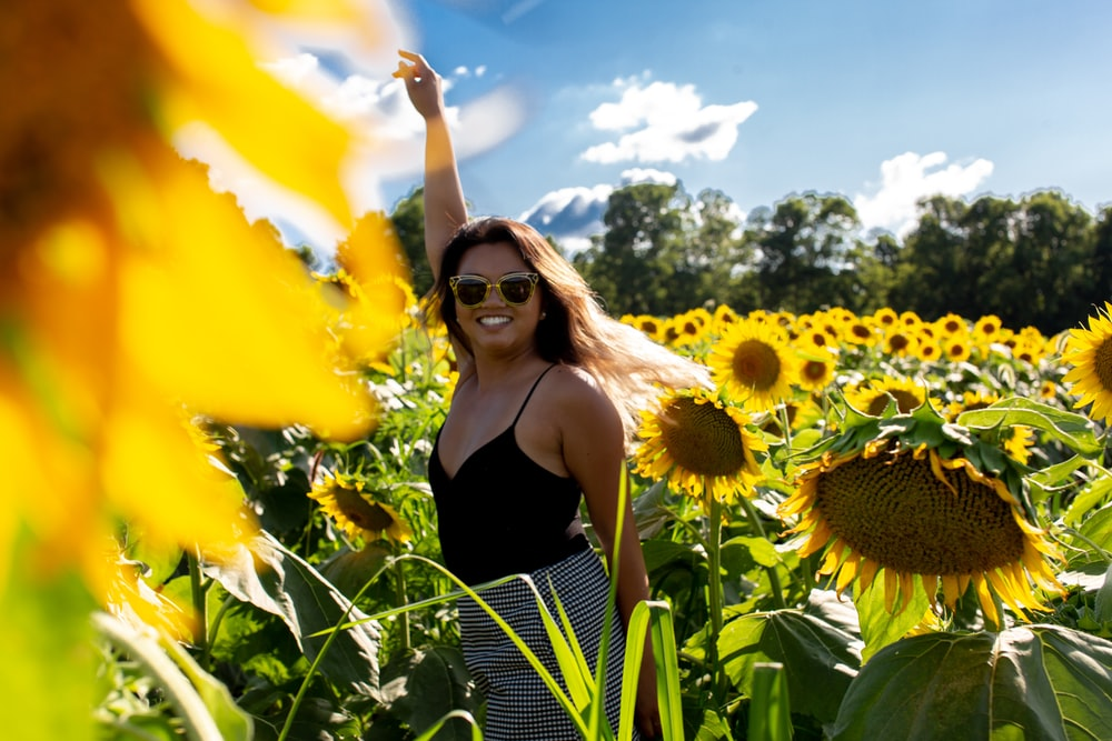 woman in black spaghetti strap blouse standing on sunflower field raising hand and smiling during daytime
