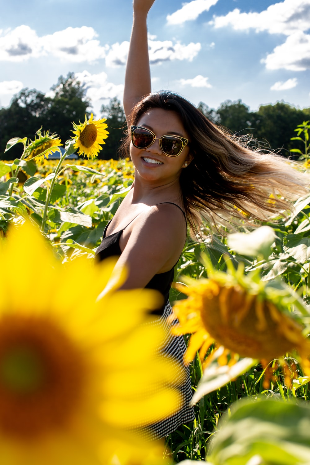 woman standing at middle of sunflower field