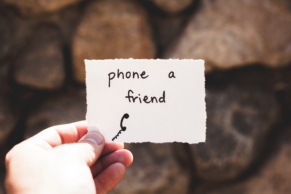 person holding piece of paper with phone a friend written text