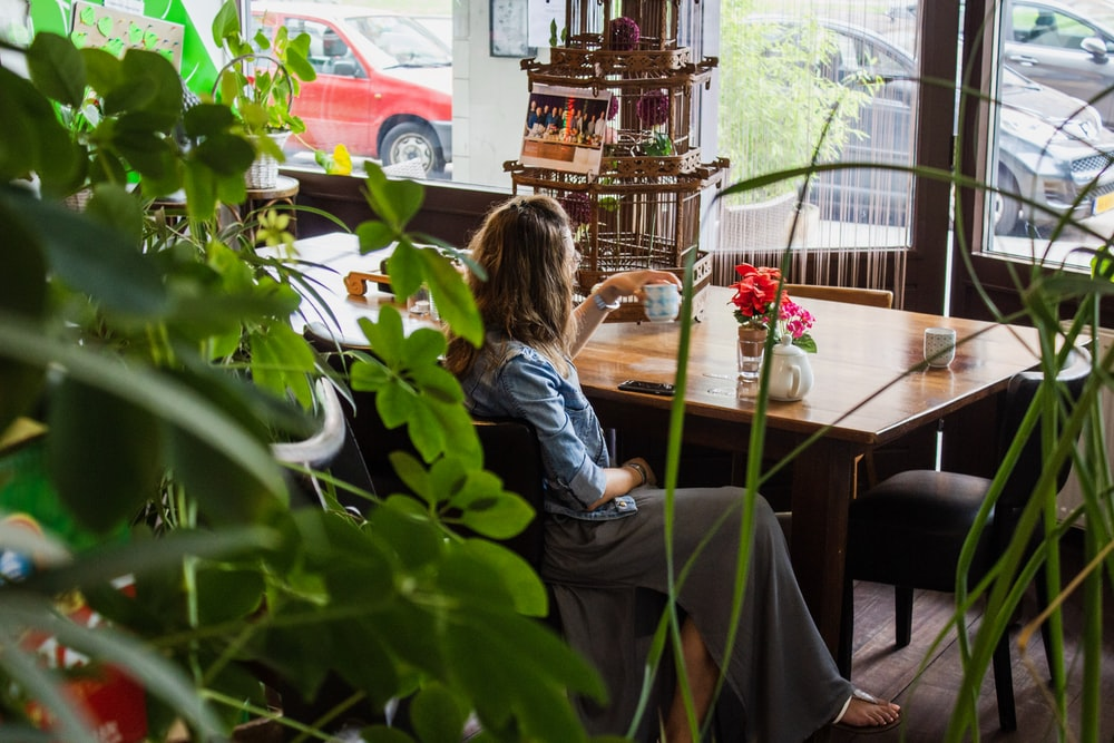 woman sitting near wooden table