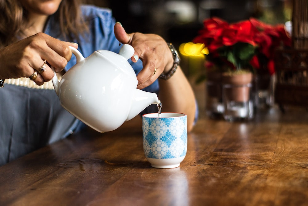 unknown person holding white ceramic kettle