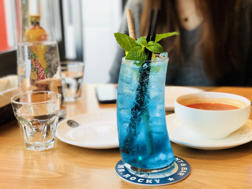 blue cocktail drink with mint on table