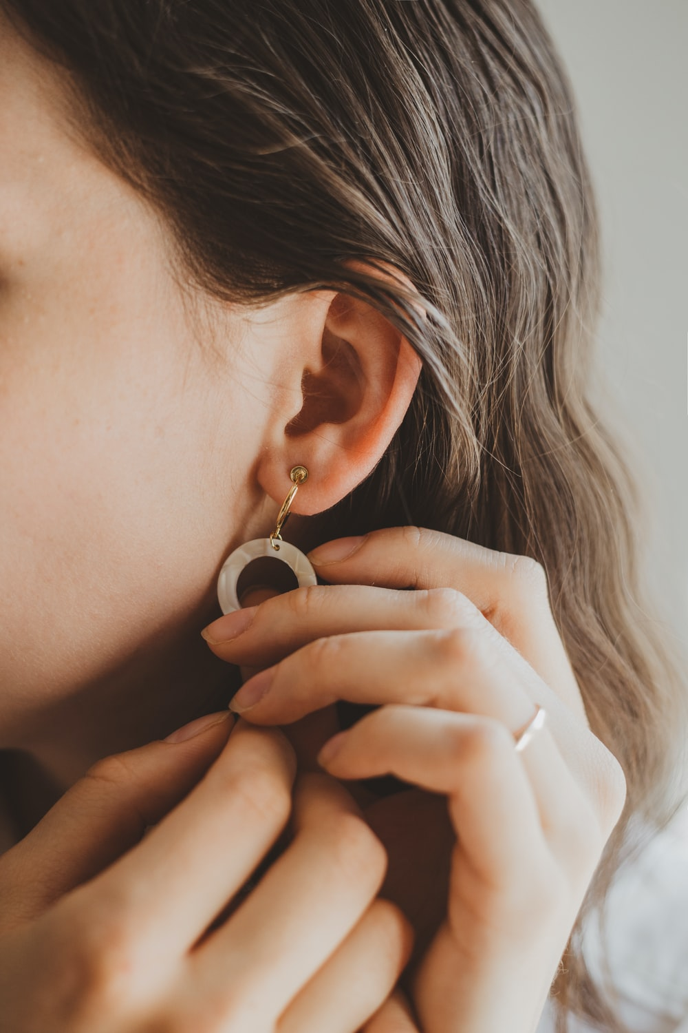 person touching earring