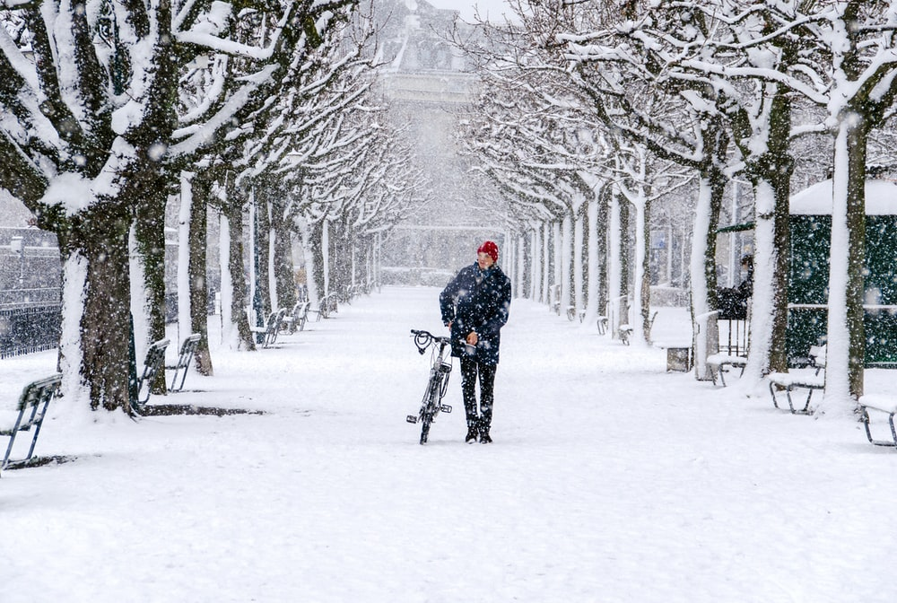 man walking with his bicycle during snow