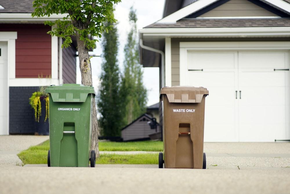 two green and brown trashbin